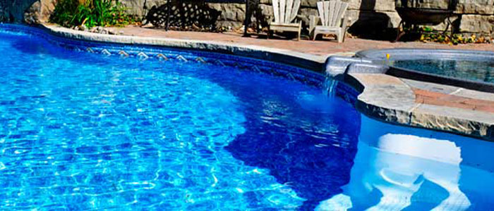 Blue colored residential pool with curved shape, with pool furniture and adjacent swimspa